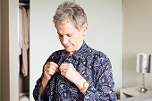 Waist up view of older woman doing up buttons on blue blouse while getting dressed in bedroom (selective focus)