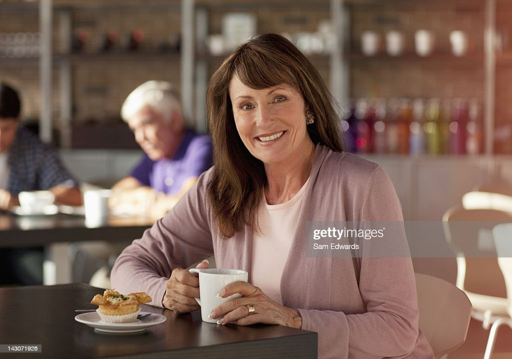 Older woman having cup of coffee in cafe : Stock Photo