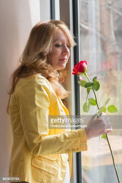 Ältere Frau mit einer roten Rose.