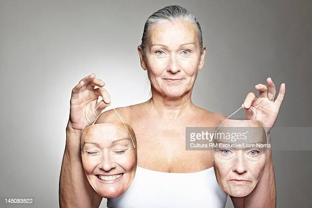 Older woman holding emotive masks