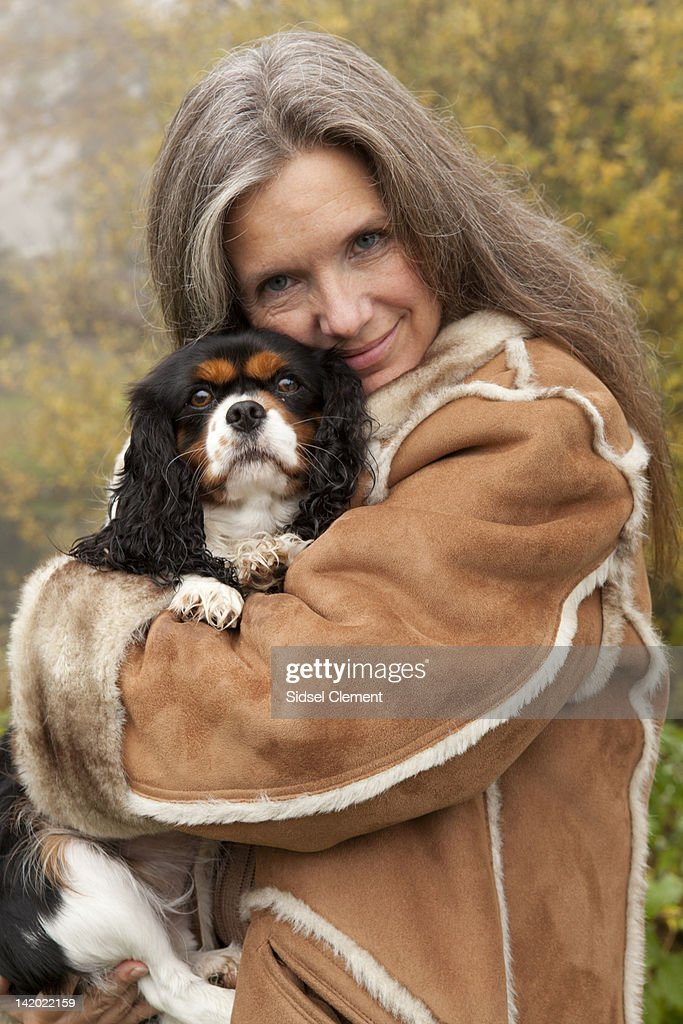 Older woman hugging dog outdoors : Stock Photo