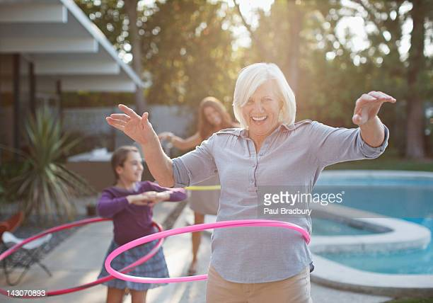 Older woman hula hooping in backyard