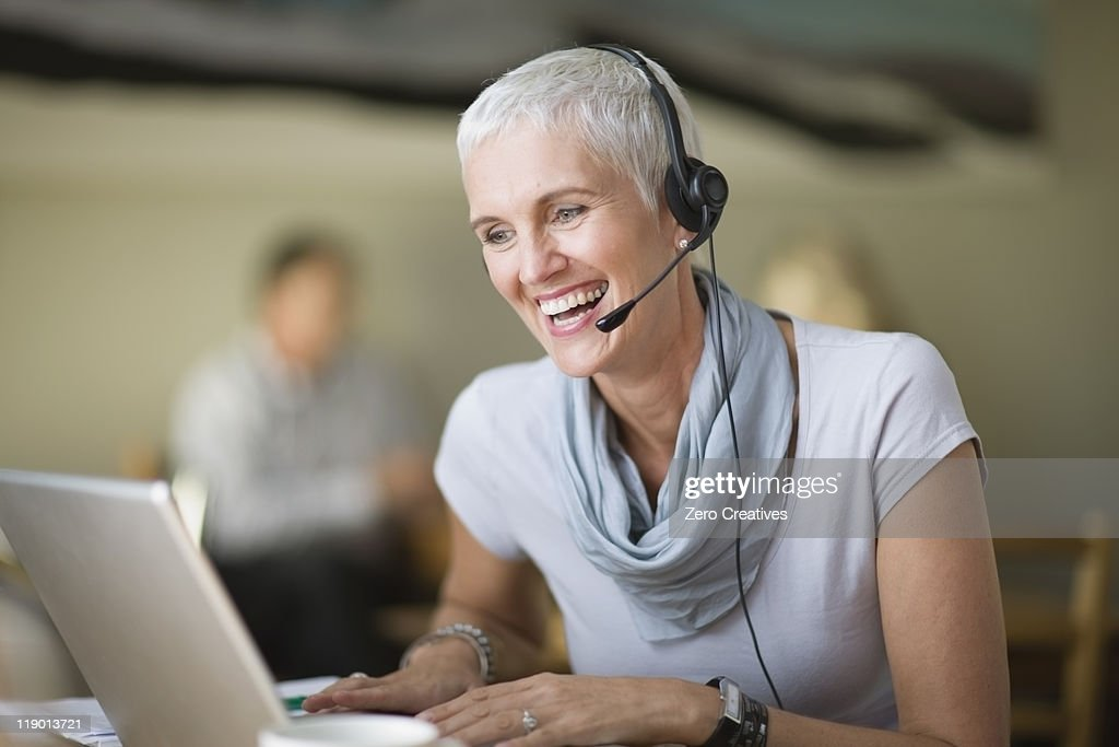 Older woman in headset using laptop