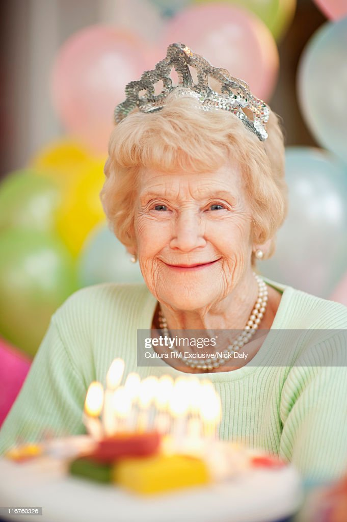 Older woman in tiara at birthday party : Stock Photo