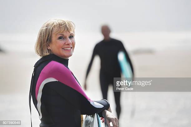 Older woman in wetsuit on beach, man in background