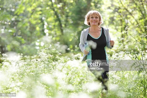 Older woman jogging through flowers