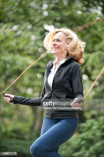 Older woman jumping rope in park