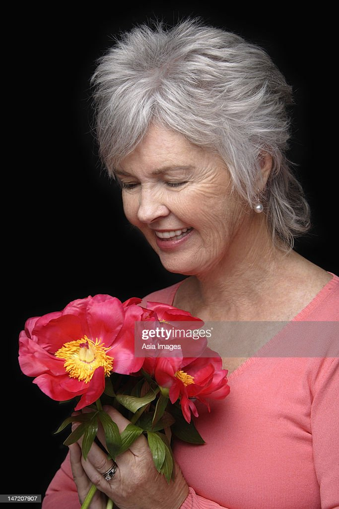 Older woman looking at bouquet of flowers. : Stock Photo