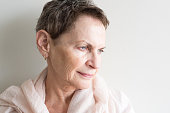 Older woman with short hair and cream scarf looking pensive (selective focus)
