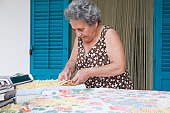 Older woman making pasta with roller