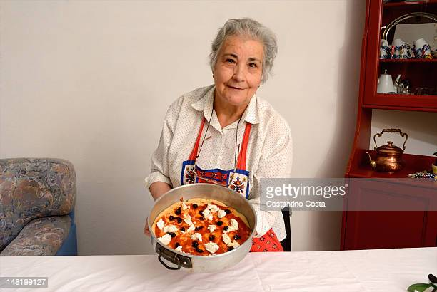 Older woman making pizza in living room