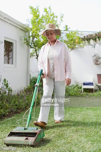 Older woman mowing lawn in backyard