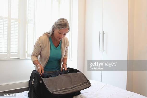 Ältere Frau mit einem Koffer packen