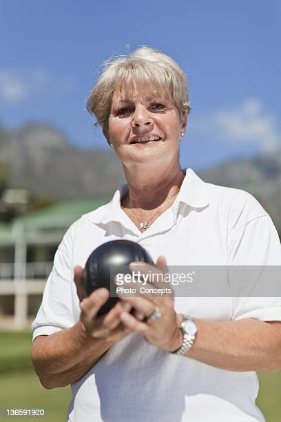 Older woman playing lawn bowling