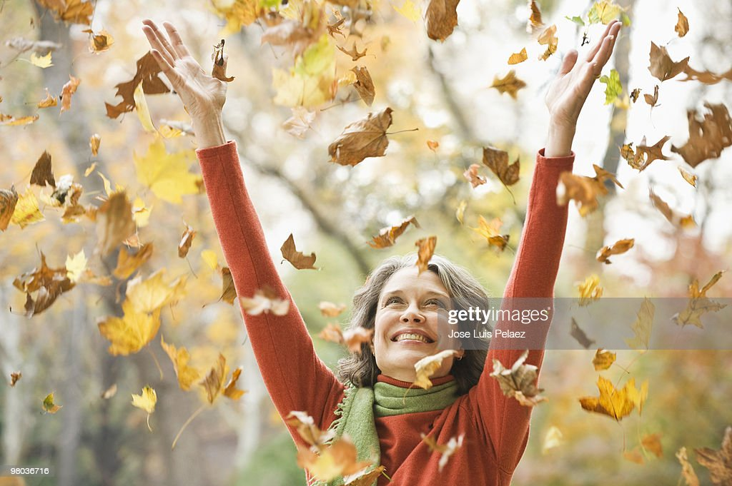 Older woman playing with leaves : Stock Photo