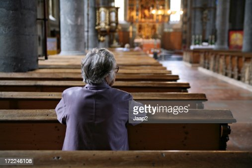 Older woman praying in an almost empty church, rear view
