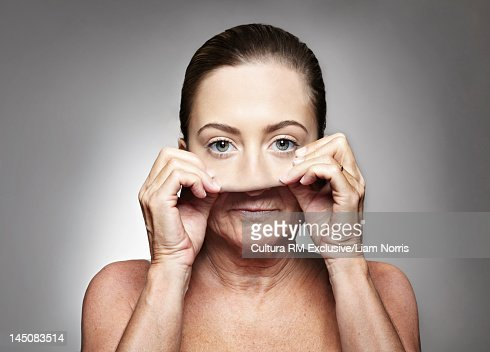 Older woman pulling on young mask