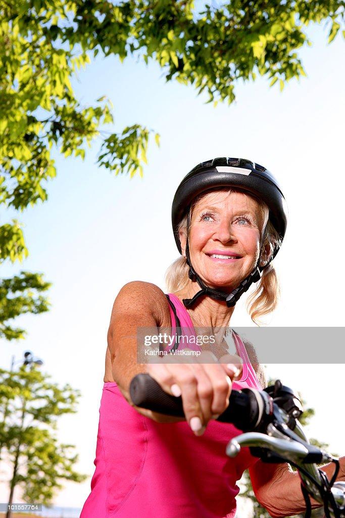 Older woman riding bike. : Stock Photo