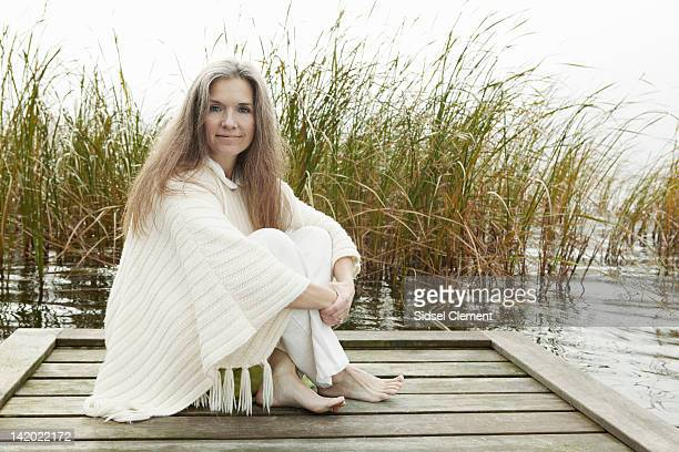 Older woman sitting on wooden dock