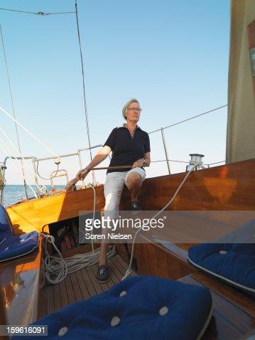 Older woman steering sailboat