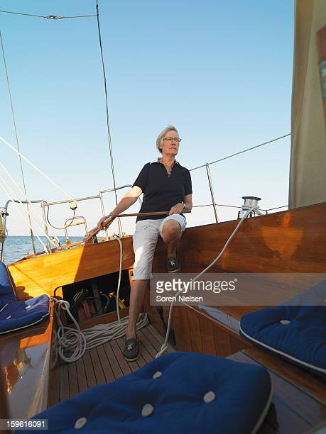 Older woman steering sailboat