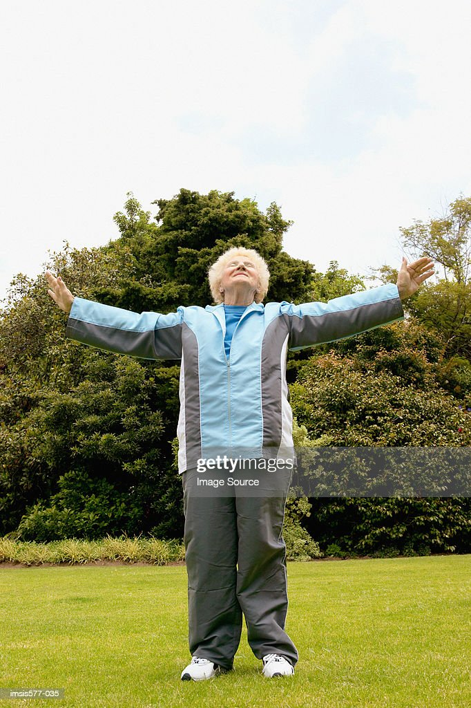 Older woman stretches outside : Stock Photo