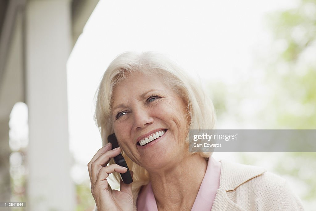 Older woman talking on cell phone outdoors : Stock Photo