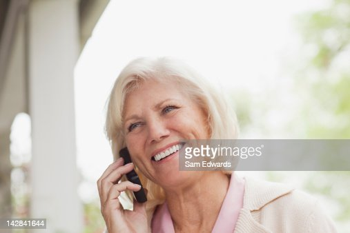 Older woman talking on cell phone outdoors : Foto stock