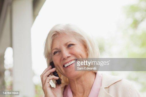Older woman talking on cell phone outdoors : Bildbanksbilder
