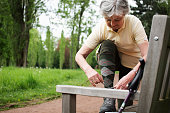 Older woman tying her shoe on bench