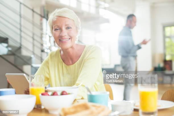 Older woman using digital tablet at breakfast table