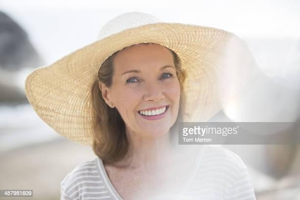 Ältere Frau mit Strohhut am Strand