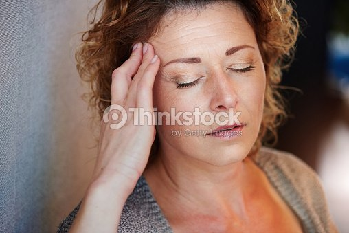 Older woman with hand to head in pain : Stock Photo