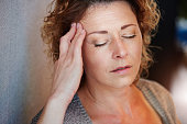 Close up portrait of older woman with hand to head in pain