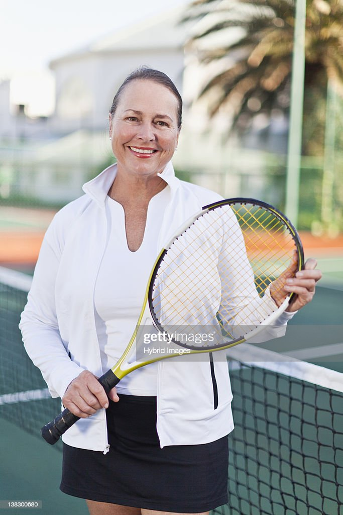 Older woman with tennis racket on court : Stock Photo