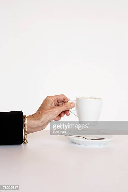 Older woman's hand holding cup of espresso.