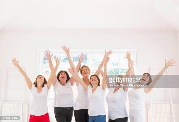 Older women cheering together indoors
