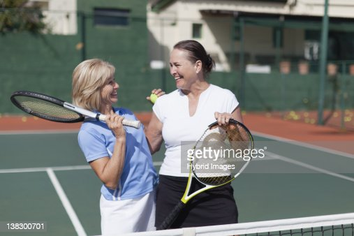 Older women hugging on tennis court