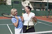 Older women hugging on tennis court