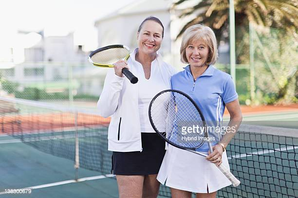 Older women with tennis rackets on court