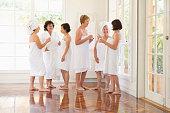 Older women wrapped in towels talking in spa