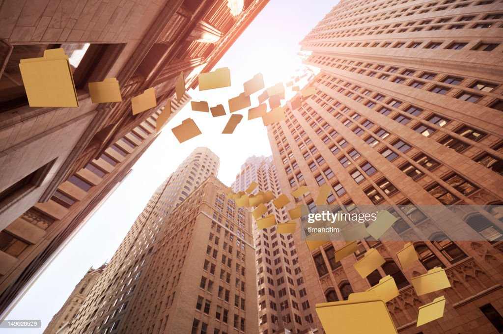 olders of documents flying among buildings : Stock Photo