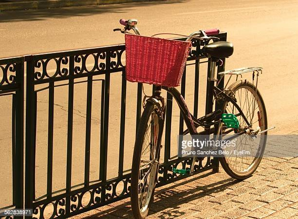 Old-Fashioned Bicycle With Basket Leaning Against Railing On Walkway