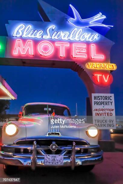 Old-fashioned car in motel parking lot at night
