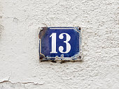 Wall of an old house in a little Bavarian town. House number 13. An old-fashioned rusty enamel sign. White number on dark blue background. Thirteen is a natural number and a prime number. In many coun