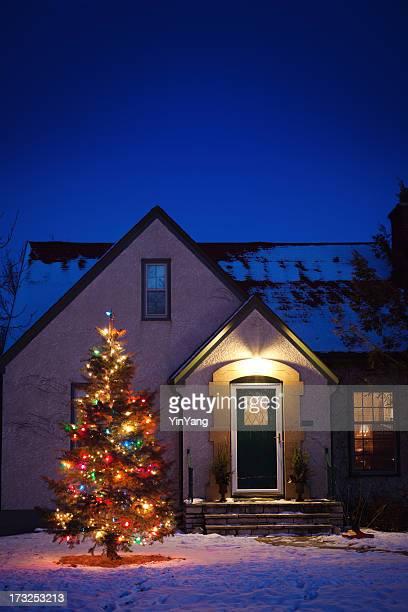 Old-fashioned Haus mit dekorierten Weihnachtsbaum Beleuchtung im Schnee Yard