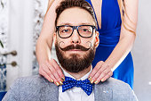 Woman with manicure straightens a bow tie to old-fashioned man in glasses with a beard and curled mustache.