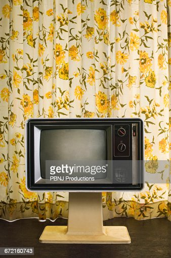 Old-fashioned television near floral curtain