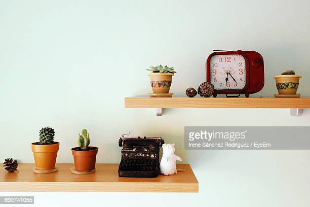Old-Fashioned Typewriter And Alarm Clock With Potted Plants On Shelves Against Wall