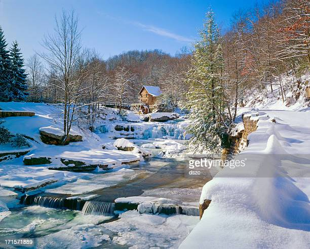 old-fashioned watermill gristmill and stream in snow